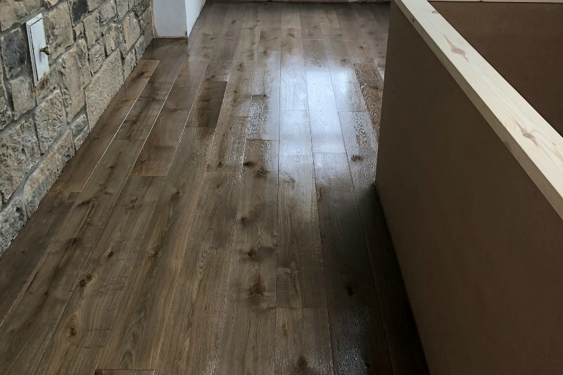 Peat colour plank floor shot with rock wall
