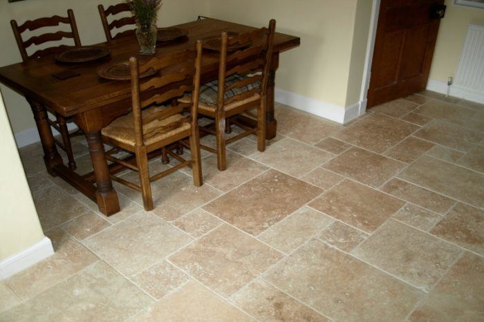 Beige travertine tile in a pattern, set in a dining area