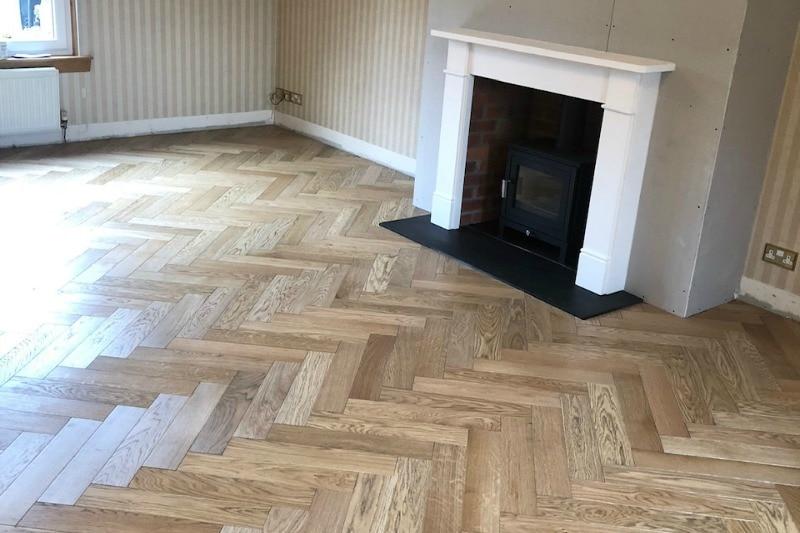 Grey oiled herringbone floor in a empty living room
