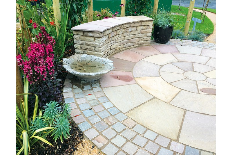sandstone circle with a border of square pathway setts in a colourful flower garden