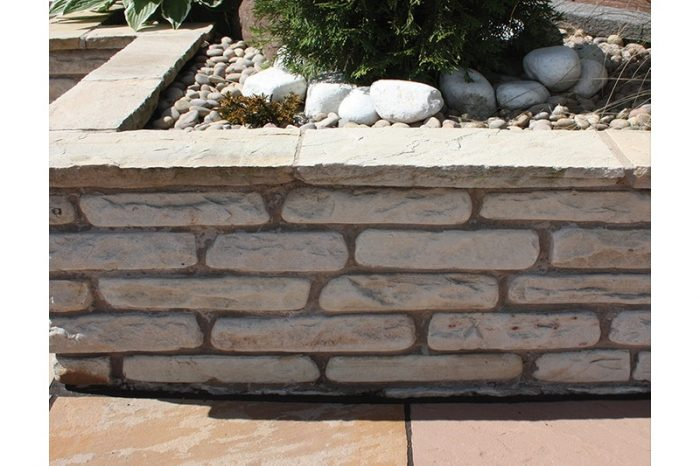 light coloured sandstone wall that encases a flower bed