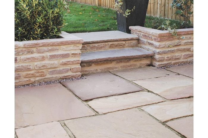 pink aged walling with a paved patio in front and steps going up to a grassed garden
