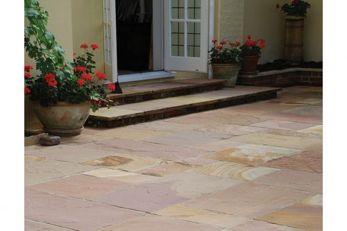 pink sandstone paving with an open door in the background