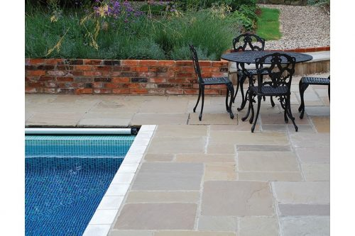 aged sandstone paving featuring a pool and dining table