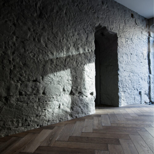 herringbone flooring scribbed to stone wall