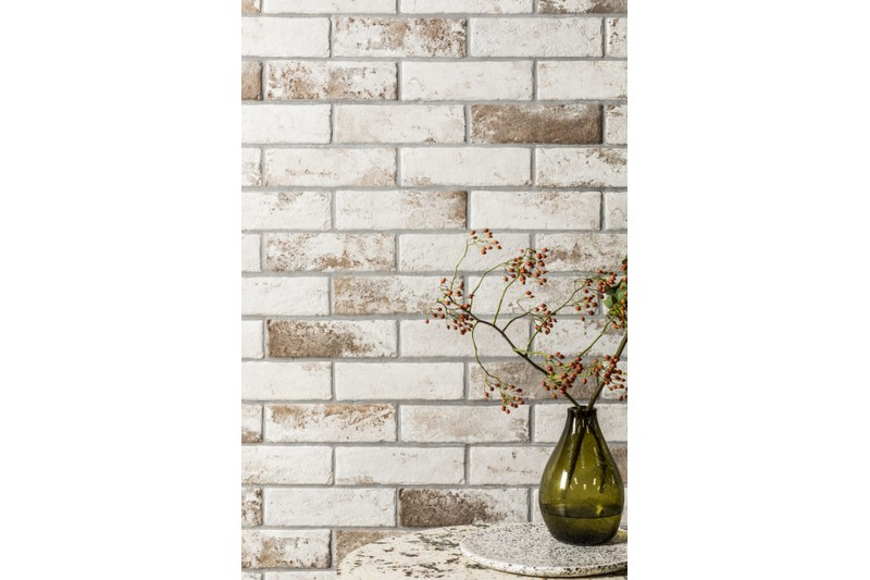 aged white brick tile with vase on table