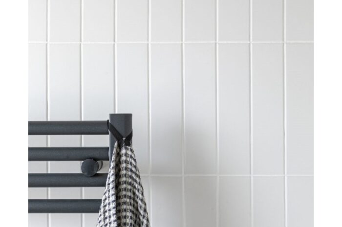 white brick porcelain tiled on wall with black radiator in fore ground