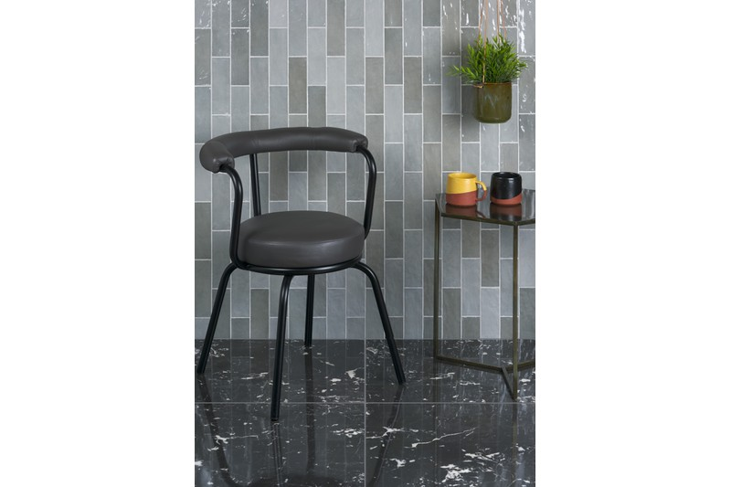 grey wall tiles with chair in foreground